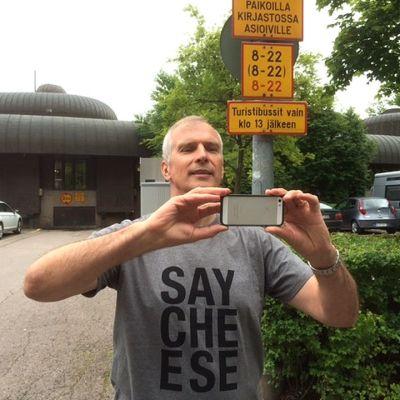 Raimo Korpela Valokuvausseurasta katukuvatapahtumasta ottaa kuvaa kännykällä pääkirjasto Metson pihassa.