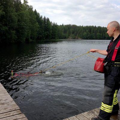 Pelastuslaitoksen narumies varmistaa että pintapelastaja ui oikeaan suuntaan harjoituksessa Suolijärvellä