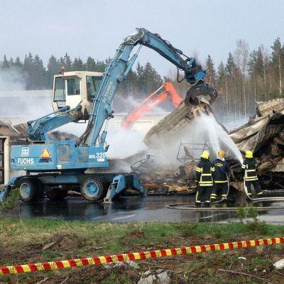 Palomiehet sammuttavat savuavia raunioita