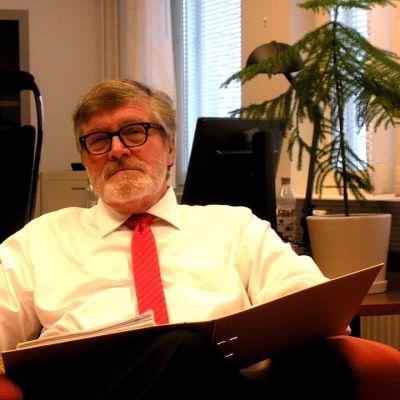 Eläkkeelle jäävä laamanni Ville Konsén istuu työhuoneensa nojatuolissa Oulun käräjäoikeudessa.