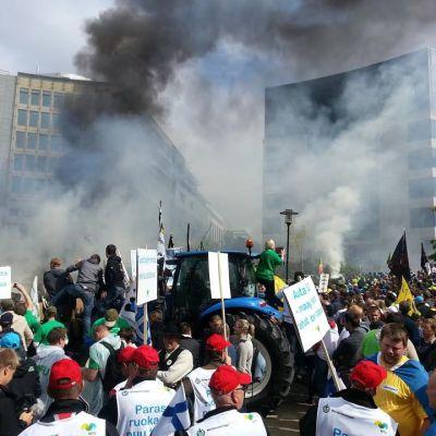 Mielenosoittajat Brysselin keskustassa savun keskellä.