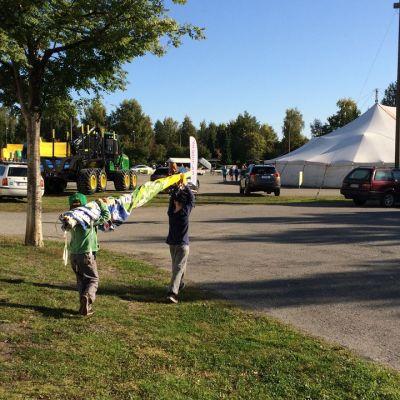 Kaksi alakoululaista kantaa pientä lipputankoa ja sen ympärille kiedottua viiriä välissään.