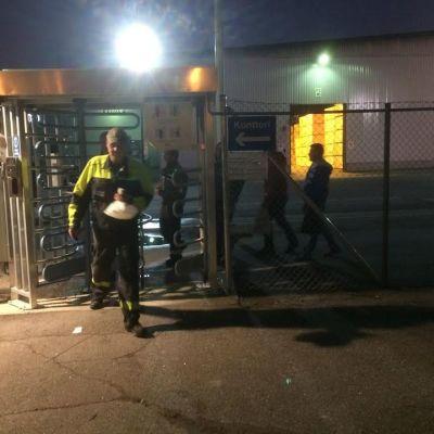Työntekijät lähtevät yövuorosta Pelloksen vaneritehtaiden portilla.
