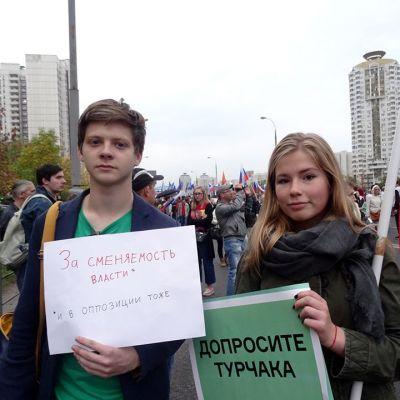 kaksi nuorta opiskelijaa pitelee plakaateja