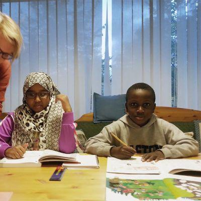 Nainen auttaa maahanmuuttajalapsia kotiläksyissä.