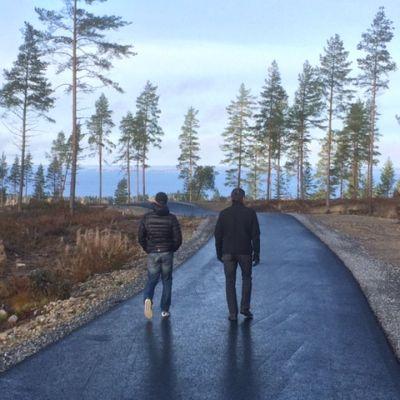Kalle Lassila ja Markku Koivumäki kävelevät asvatoidulla hiihtoradalla. Taustalla Lappajärvi.