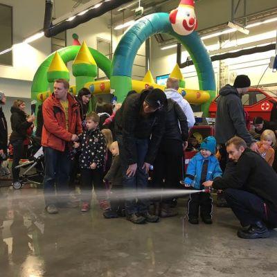 Perheitä seuraamassa kun palomies Aki Niskanen esittelee, miten vesi suihkuaa paloletkusta Päivä paloasemalla -tapahtumassa.