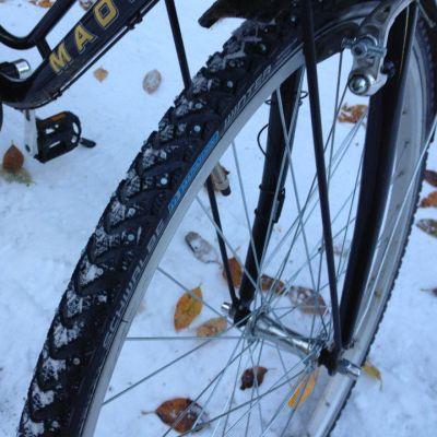 Polkupyörän nastarengas lumisella tiellä