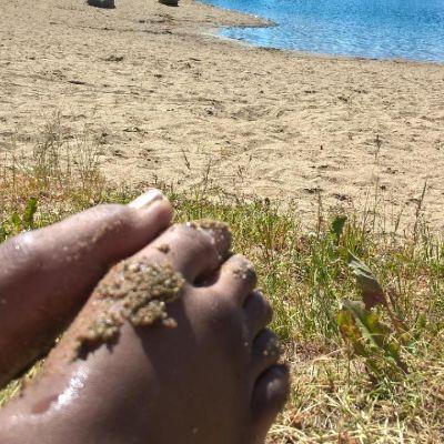 Lapsen hiekkaiset varpaat uimarannalla.