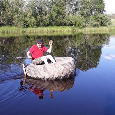 Mies ajaa joella traktorinrenkaalla