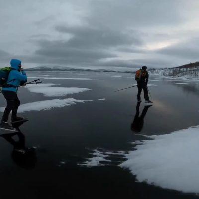 Retkiluistelijat kiitävät peilikirkkaalla Kilpisjärven jäällä