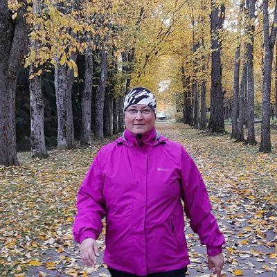 Kvinna i lila jacka som går bland höstgula träd.