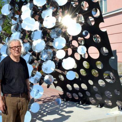 Taiteilija Pauno Pohjolainen seisoo Keko-taideteoksensa edustalla.