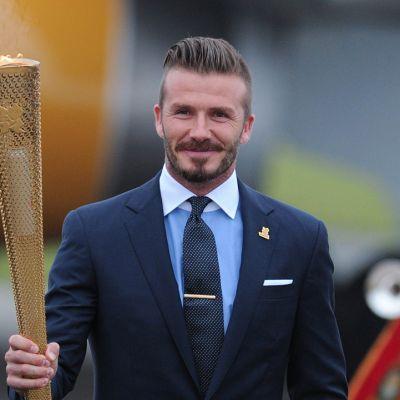 David Beckham olympiatuli kädessään