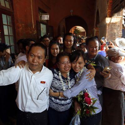 Etualalla mies nostaa ruusukimppua kohti kameraa; kaksi naista halaa. Taustalla ihmisjoukkoa.