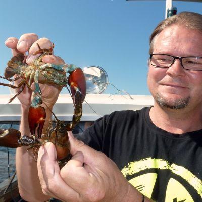 Kalatalousneuvoja Petri Mäkinen pitää käsissään kahta rapua