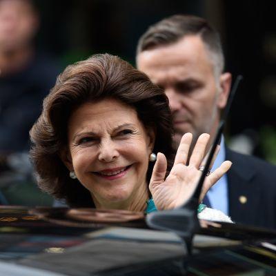 Silvia vilkuttaa lehdistölle, taustalla kaksi turvamiestä.