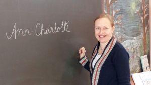 Ann-Charlotte Aminoff skriver sitt namn på svarta tavlan i klassrummet.
