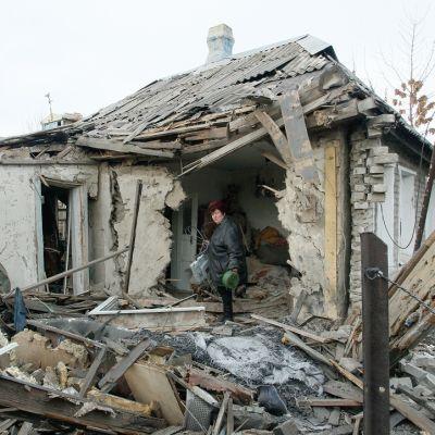 Nainen seisoo hajonneen talon reunalla.