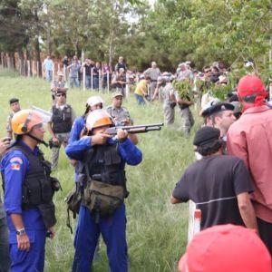 Brasilialaiset poliisit aseiden kanssa, maattomat maatyöläiset aidan takana.