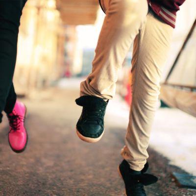 Vaaleanpunaisiin ja sinisiin kenkiin sonnustautuneet lapset juoksevat kadulla.