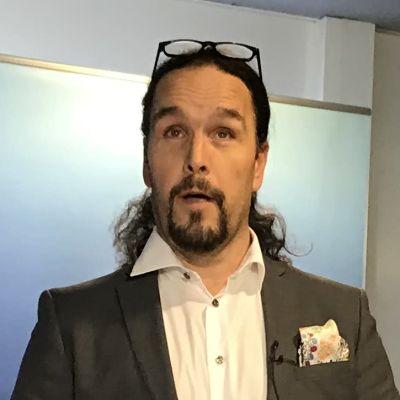 Fredrik Karlström står vid ett högt bord med en mikrofon framför sig.