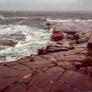 Myrskyinen meri, pieni puuvene kiinnitettynä kallioon.