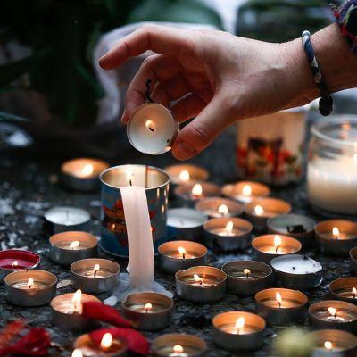 Nainen sytyttää kynttilöitä veritahrojen päälle Bataclanin konserttitalon lähellä Pariisissa 14. marraskuuta.