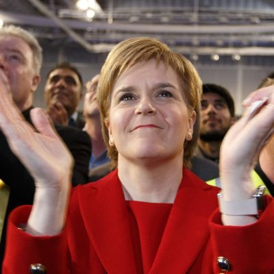 Hymyilevä Sturgeon taputtaa käsiään puoluetoverien ympäröimänä.