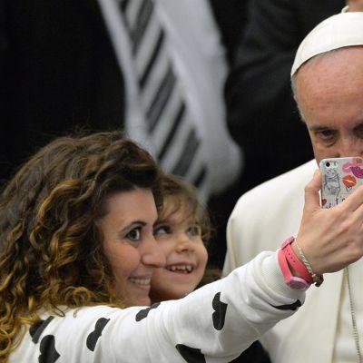 Paavi Franciscus poseeraa selfie-kuvaan.