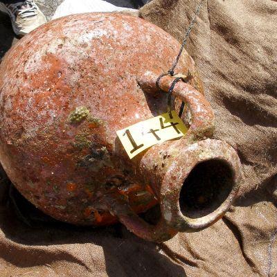 Ruskea keramiikka-amfora kyljellään säkkikankaan päällä.