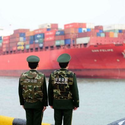 Kiinalaisia rajavartijoita satamassa odottamassa rahtilaivaa.