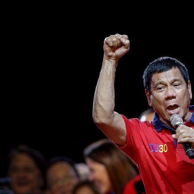 Duterte puhuu vasemmassa kädessään olevaan mikrofoniin ja pitää oikeaa kättään nyrkissä.