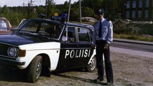 Bild från 70-talet. En ung polis står vid sin bil.