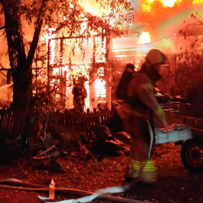 Palomiehet sammuttamassa ilmiliekeissä olevaa ulkovarastoa.