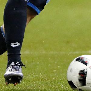 en fotbollsspelare och en fotboll.