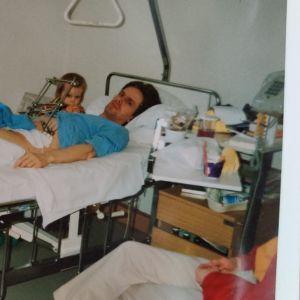 Man ligger i sjukhussäng