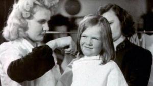 Nuoren tytön hiuksia leikataan jatkosodan aikana