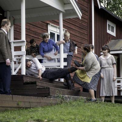 Egon (Ulf Johansson) förs hastigt hem mitt i slåttern. Hustrun Ester (Anci Holm) hjälper till. T v sonen Orvar (Arttu Flén). Foto: Johanna Överfors