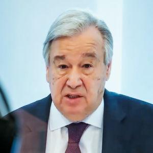FN:s generalsekreterare Antonio Guterres talar under ett klimatmöte som hålls på distans. HAns ansikte syns via en skärm.