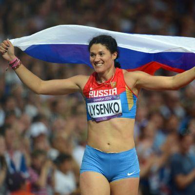 Venäjän Tatjana Lysenko poseeraa maansa lipun kanssa Lontoon olympialaisten moukarifinaalin jälkeen.