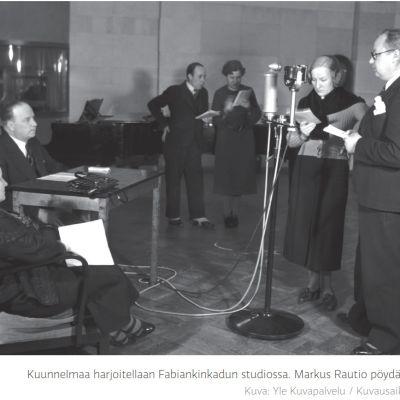 kuusi henkilöä ison mikrofonin äärellä. Mustavalkokuva vuodelta 1930.