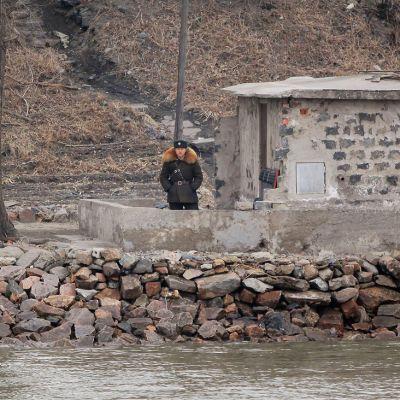 Sotilas vartiossa joen rannalla.