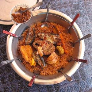 Tallrik med flera skedar dränkta i den traditionella senegalesiska maträtten Thieboudienne eller ceebu jen, som består av fisk, ris och tomatsås.