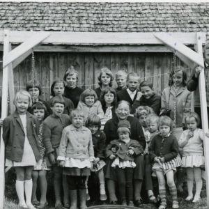 Myllykylän lapset ovat pyhäkoulussa. Virpi Talvitie on oikean alakulman tyttö, jolla on sormi suussa ja itku kurkussa. Vaikka kuvan ottamiseen liittyy pienoinen tragedia, ovat maalla vietetty lapsuus ja tämä kuva Talvitielle rakkaita muistoja.