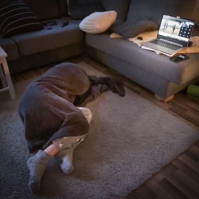 Kuva lattialle nukahtaneesta Aino Hopiasta. Sohvalla on läppäri, jossa on meneillään etätanssitunti.