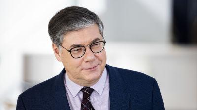 Asko Järvinen bär glasögon och en blå kostym med ljus skjorta och mörk slips.