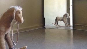 En gunghäst syns i förgrunden och som spegelbild