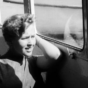 Nainen ihailee maisemia laivan ikkunasta