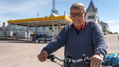 Äldre man leder sin elcykel och ser mot kameran, i bakgrunden en bensinmack i centrum av Hangö.